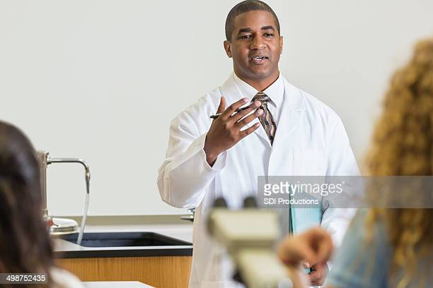 High school science teacher explaining experiment to students in classroom