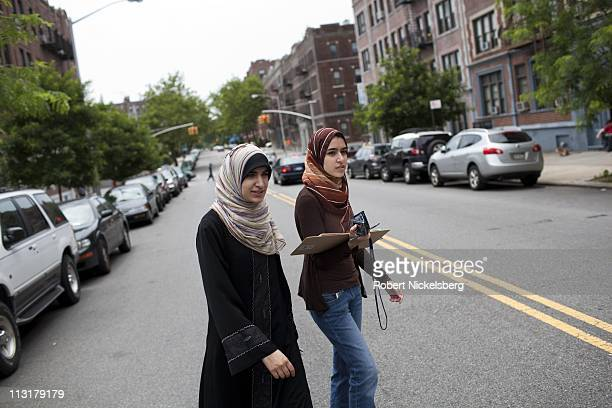 High school senior Asmaa Rimawi left crosses a street with her older sister Fatimah right while working with a Democratic Party voters list during a...