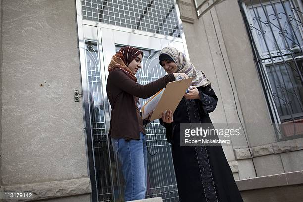 High school senior Asmaa Rimawi right checks a Democratic Party voters list during a petition drive for party candidates with her older sister...
