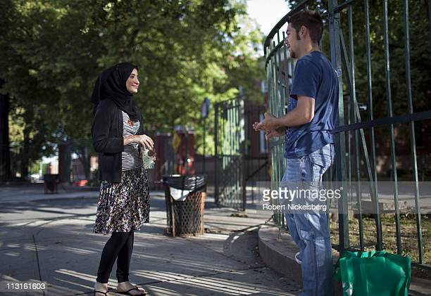 High school senior Dania Darwish, 17 years, left, speaks with one of her classmates June 11, 2010 in front of the Fort Hamilton High School in...