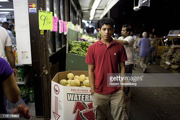 High school senior Mohamed Amin, 18 years, stands near a busy food market July 8, 2010 in Jackson Heights, New York. Mohamed graduated from the...