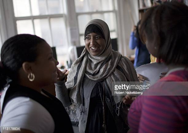 High school senior Sharmin Hossain, 17 years, center, speaks with two of her student colleagues at her job as a student community organizer May 17,...