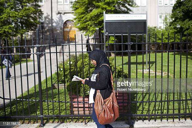 High school senior Sharmin Hossain reads a magazine May 11, 2010 in front of her school in Queens, NY. She spends 90 minutes traveling each way to...
