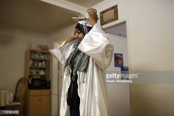 High school senior Sharmin Hossain tries on a graduation cap June 23, 2010 in her Queens, New York home before attending her high school graduation...