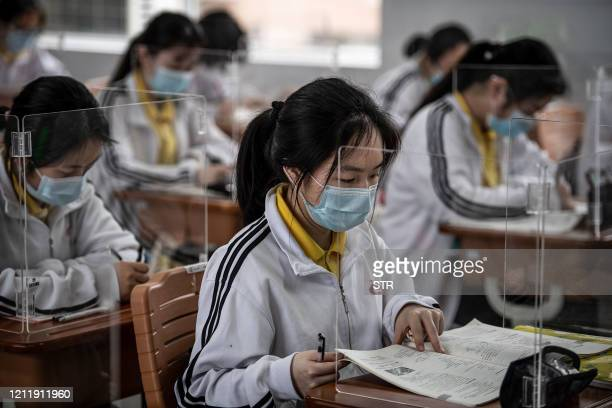 High school senior students study with plastic partitions in a classroom in Wuhan in China's central Hubei province on May 6, 2020. - Senior school...
