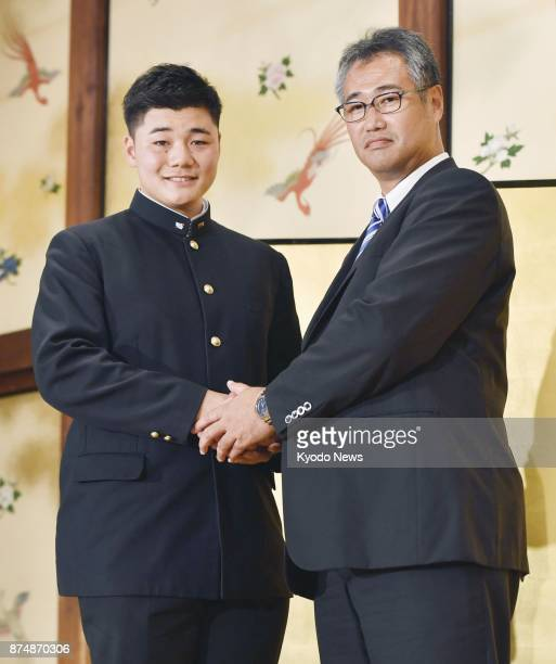 High school slugger Kotaro Kiyomiya the most soughtafter player in October's amateur draft shakes hands with Nippon Ham Fighters acting general...