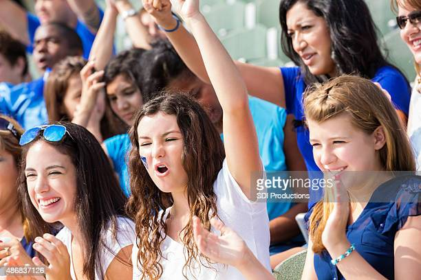 high school sports fans cheering for team in stadium - high school football stock pictures, royalty-free photos & images
