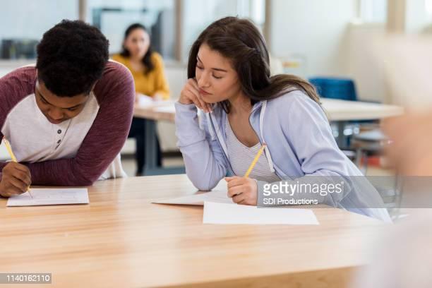 high school student cheats op test - oneerlijkheid stockfoto's en -beelden