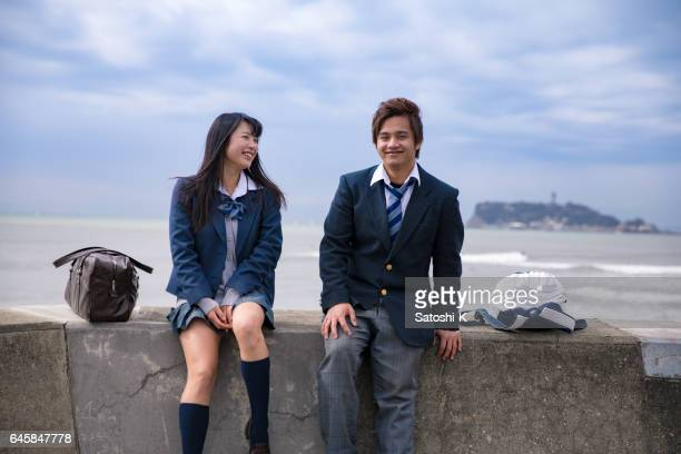 High school student couple being relaxed at beach
