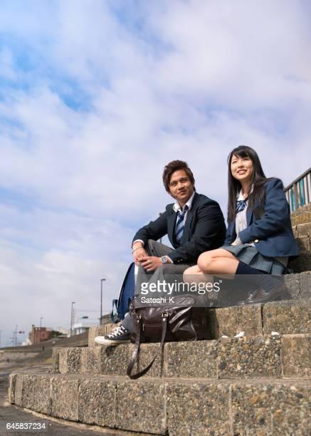 ビーチで階段に座っている高校生カップル