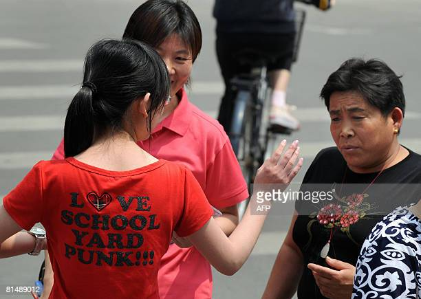 A high school student gestures while talking with her mother outside the Chenjinglun High School following a session of the national college entrance...