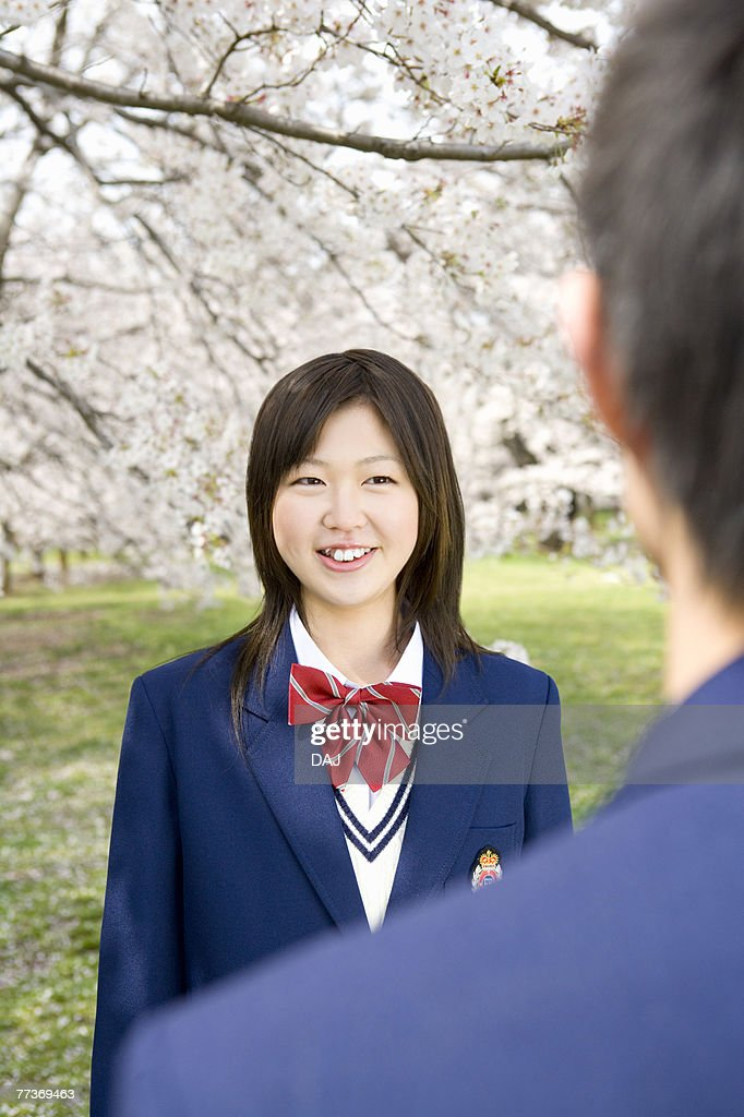 High School Student Girl Talking in Field with Cherry Blossom in the Background, Differential Focus : Photo