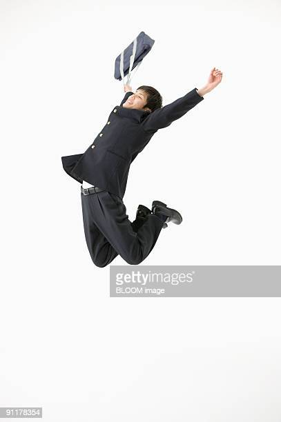 High school student jumping, holding bag, studio shot