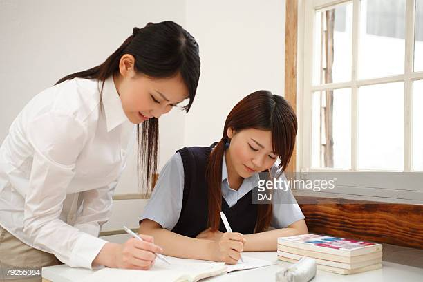 high school student learning study from sister - teacher bending over stock photos and pictures
