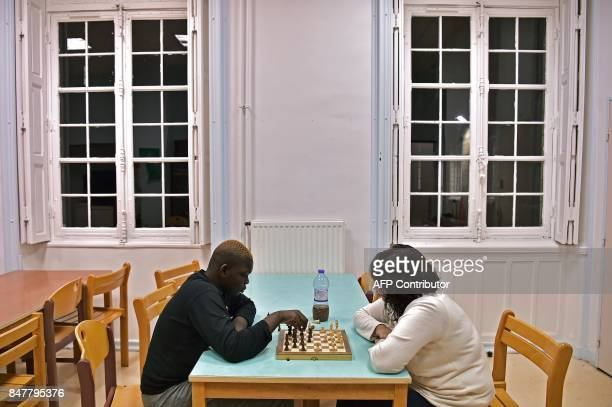 A high school student plays a board game with an educator in the evening at the common room of the boarding school at the Apprentis d'Auteuilmanaged...