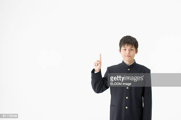 high school student pointing upward, portrait, studio shot - ユニフォーム ストックフォトと画像