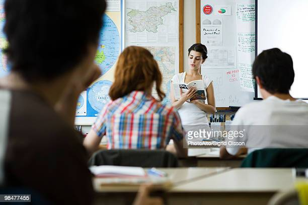 High school student reading book aloud to class