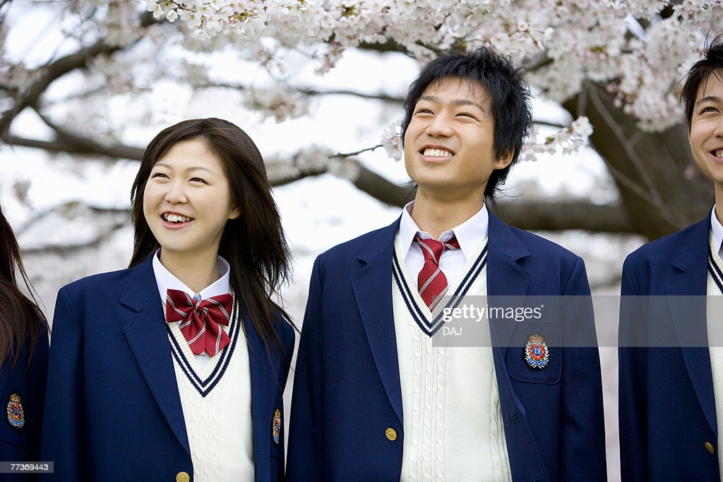 High School Student Standing in Front of Cherry Blossoms : Photo