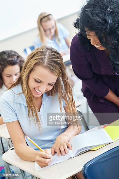 High school student working on work with teacher helping