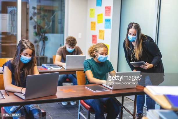 high school students and teacher wearing face masks and social distancing in classroom setting working on laptop technology - classroom stock pictures, royalty-free photos & images