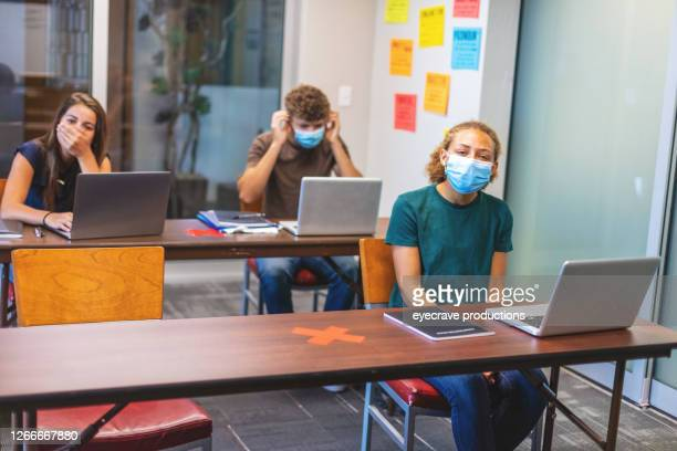 high school students and teacher wearing face masks and social distancing in classroom setting working on laptop technology - eyecrave  stock pictures, royalty-free photos & images