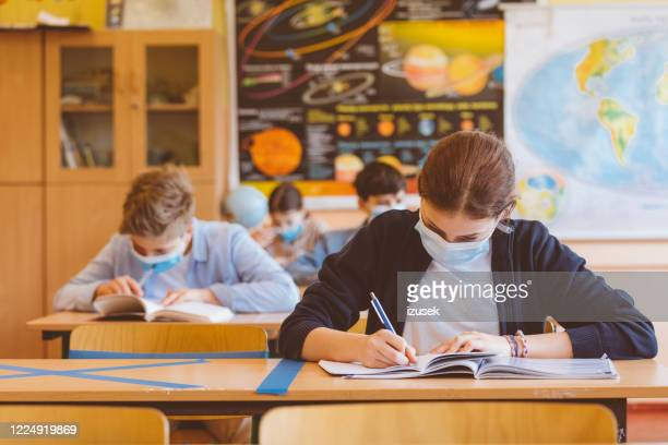 high school students at school, wearing n95 face masks. - school child stock pictures, royalty-free photos & images