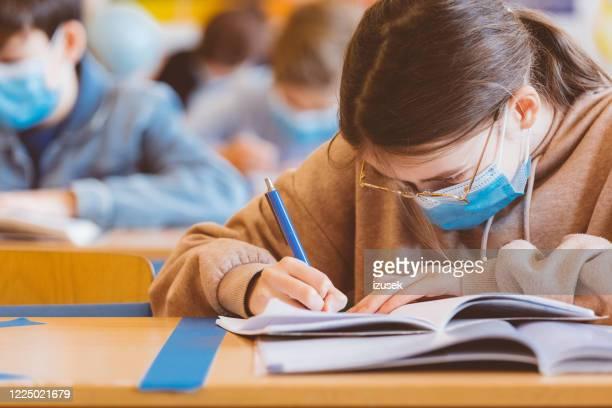 estudiantes de secundaria en la escuela, usando máscaras faciales n95. - izusek fotografías e imágenes de stock