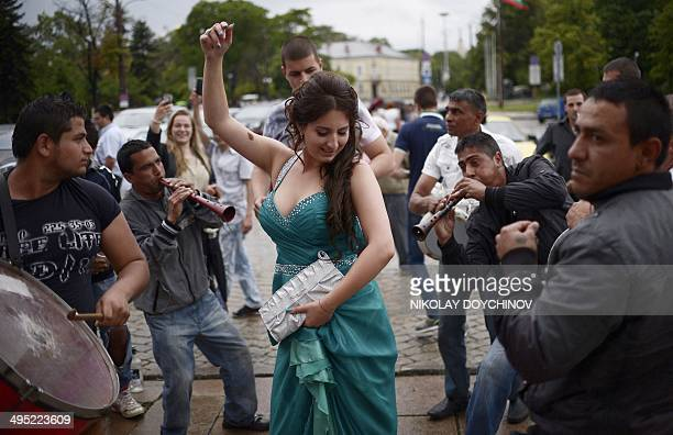High school students celebrate their graduation with musicians in front of the goldendomed Alexander Nevsky Cathedral in Sofia on May 27 2014 Honking...