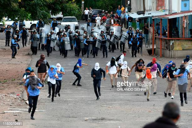 High school students clash with riot police during a protest to demand the resignation of Honduran President Juan Orlando Hernandez in Tegucigalpa on...