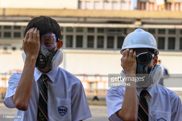 TOPSHOT High school students cover their right eye after a woman suffered an eye injury which demonstrators blamed on a beanbag round fired by police...