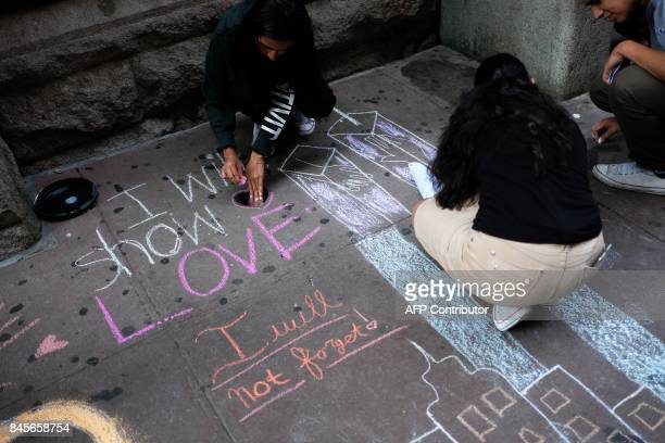 High school students draw the Twin Towers and write messages on the sidewalk in front of their school on September 11 2017 in New York in observance...