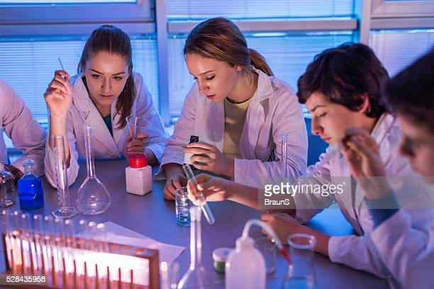 High school students having a chemistry class in laboratory.