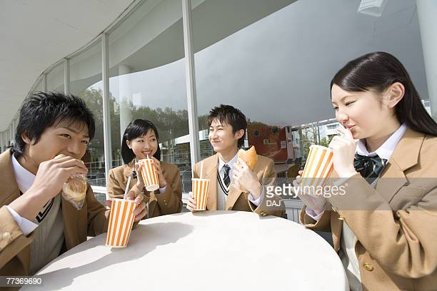 High school students having lunch at terrace, smiling