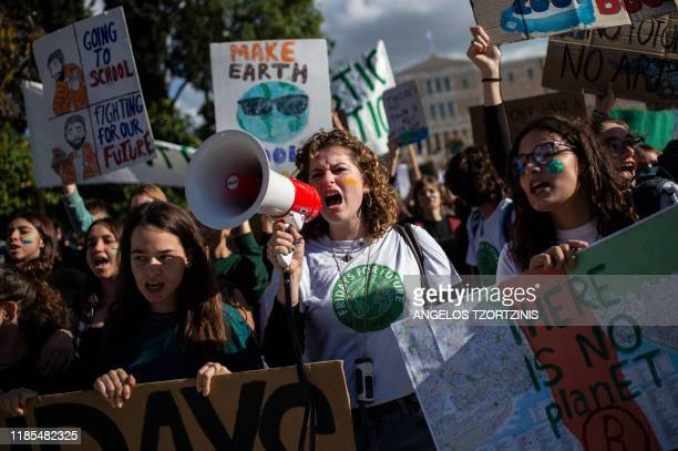 High school students hold placards and shout slogans as they take part in a demonstration of the Fridays for Future movement for climate protection...