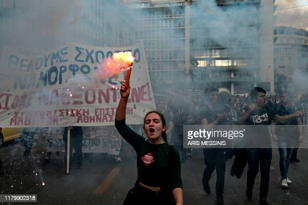 High school students light flares while demonstrating in central Athens on November 4 against the shortage of teachers in schools and the upcoming...