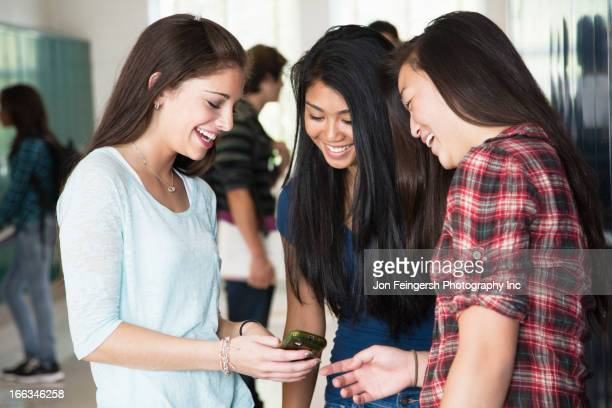 High school students looking at cell phone together