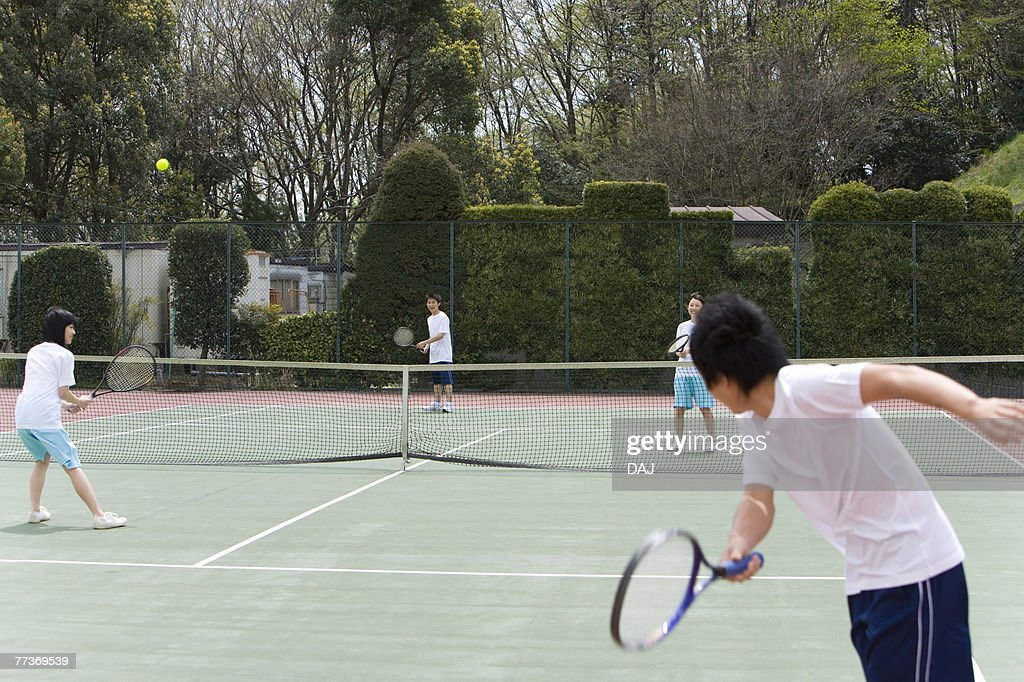 High School Students Playing Tennis on Ground : Photo