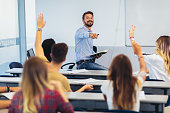 High school students raising hands on a class