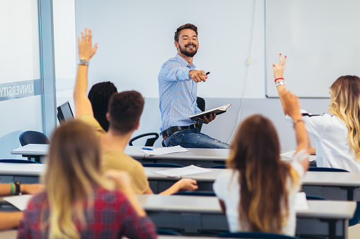 High school students raising hands on a class 1177608272