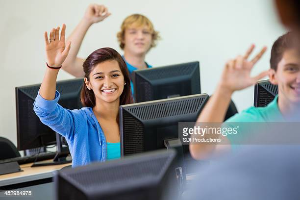 High school students raising hands to answer question in class