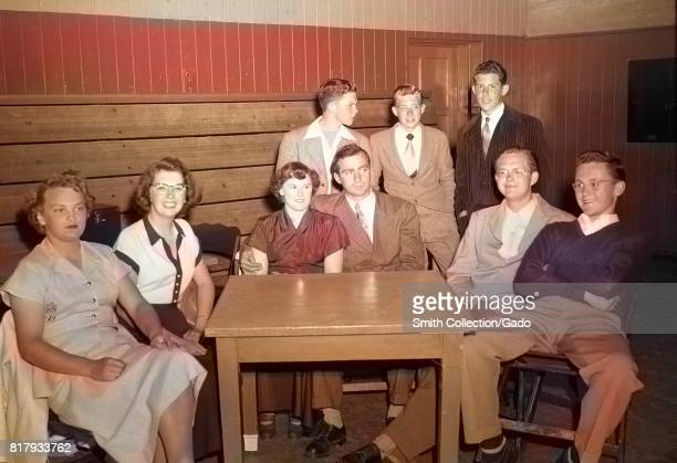 High school students sit at a small table in a gymnasium during a high school dance with two people in a couple and others smiling or standing...