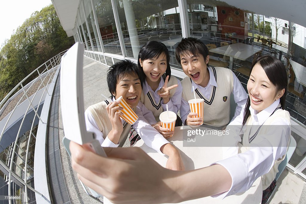 High school students smiling and photographing with mobile phone, fish-eye lens : Photo