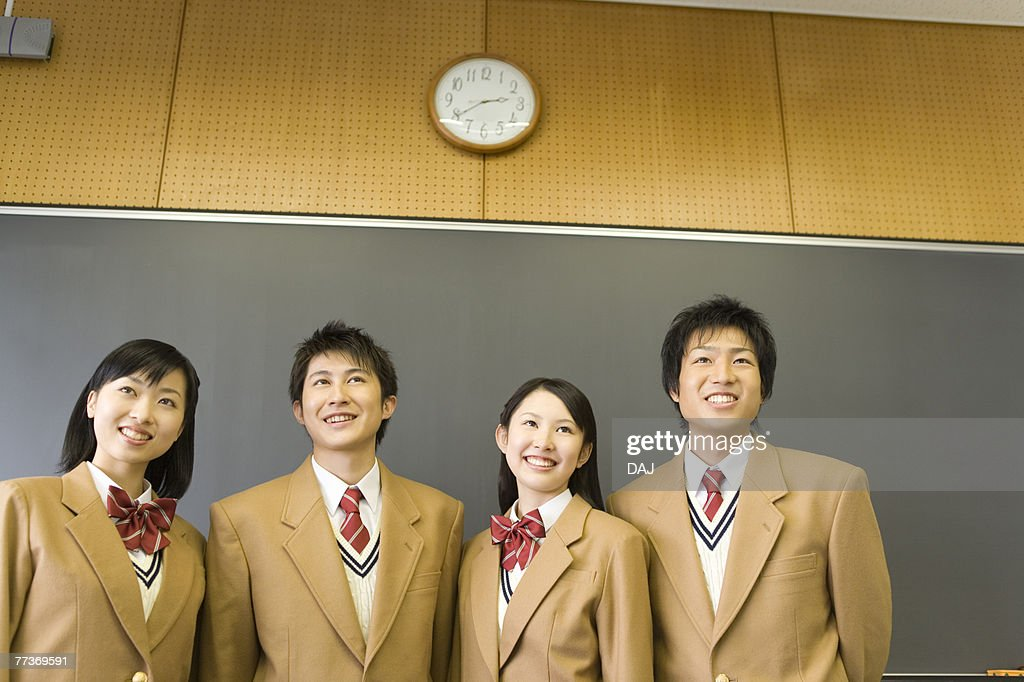 High School Students Standing and Smiling in front of Blackboard : Photo