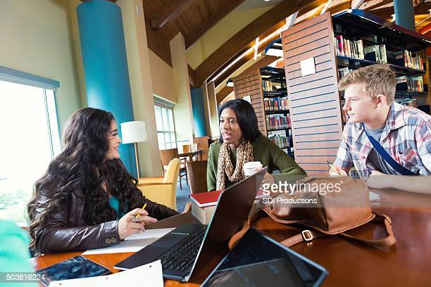 High school students studying for exam together in modern library