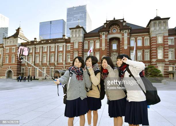 High school students take a selfie at the square in front of JR Tokyo Station with the redbrick Marunouchi Station Building in the background on Dec...