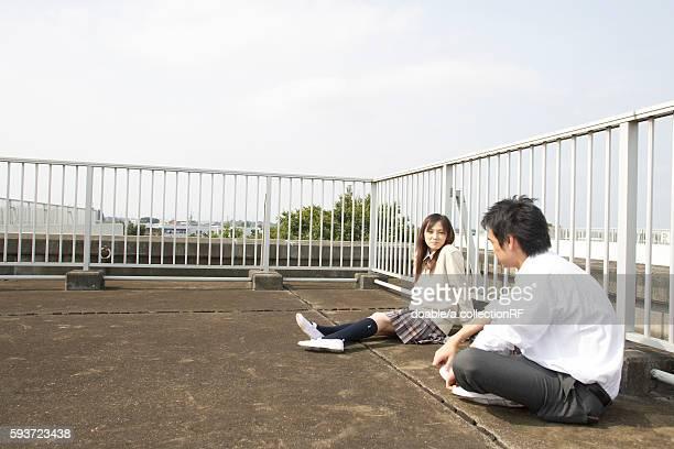 high school students talking on rooftop, japan - 柵 ストックフォトと画像
