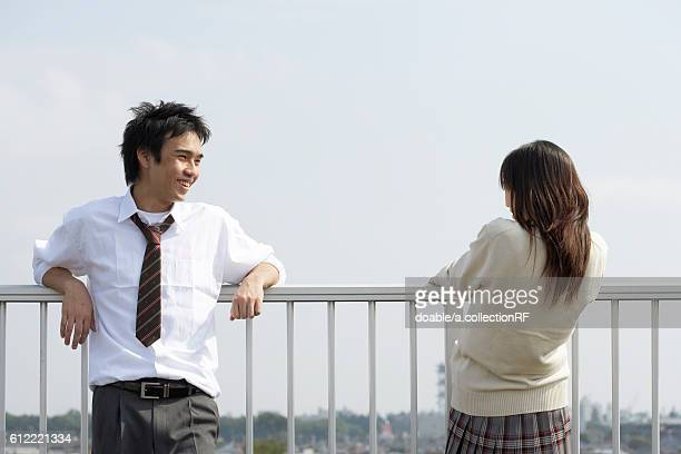 High school students talking on rooftop, Japan
