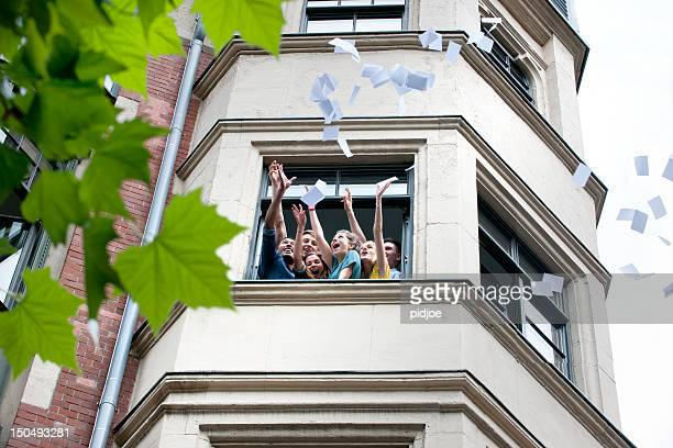 high school students throwing paper out of window