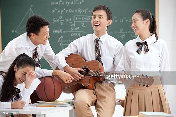High school students to play the guitar in the classroom
