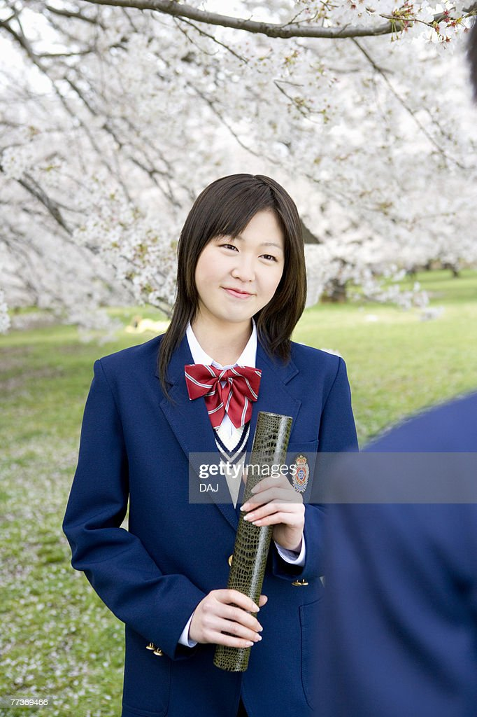High School Students Under Cherry Blossoms with Holding Diploma : Photo